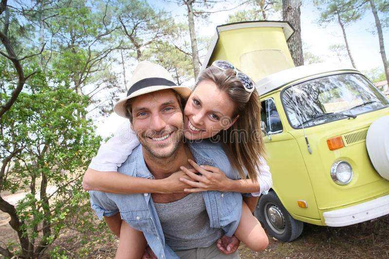 Happy young couple in front of camping van stock image
