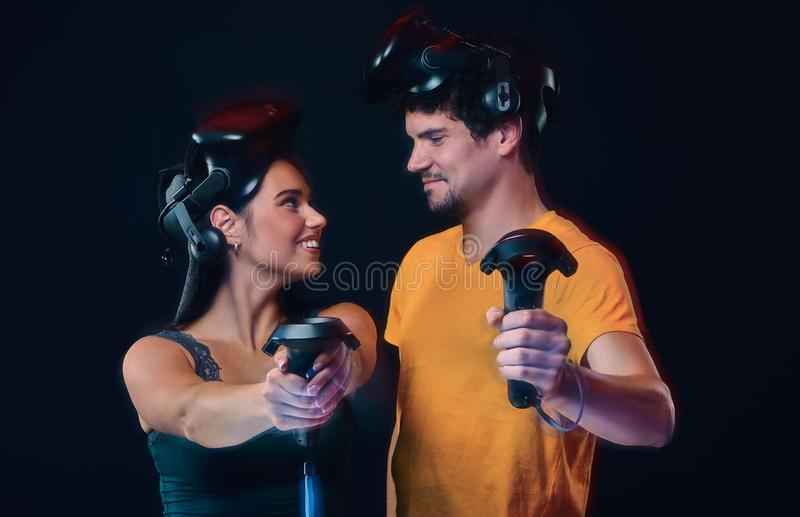 Happy young couple of gamers posing with virtual reality goggles and controllers. Isolated on dark background royalty free stock images