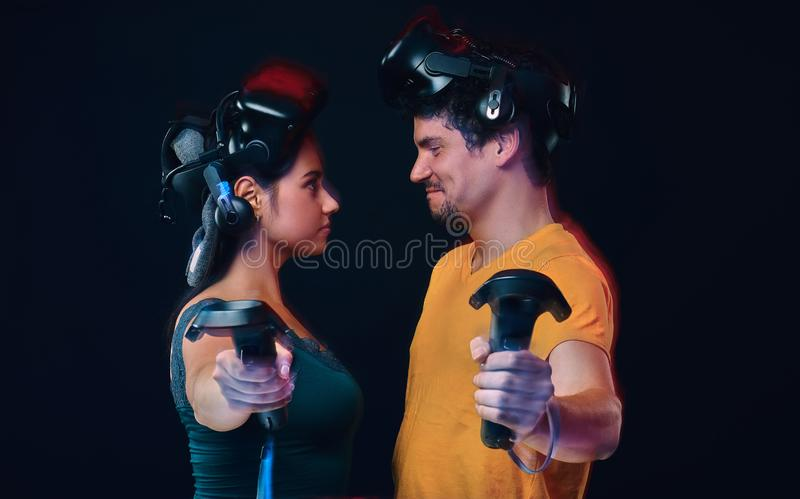 Happy young couple of gamers posing with virtual reality goggles and controllers. Isolated on dark background royalty free stock photo