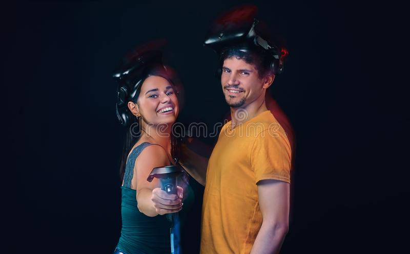 Happy young couple of gamers posing with virtual reality goggles and controllers. Isolated on dark background royalty free stock photography