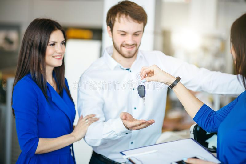 Happy young couple getting keys of their new car at dealership stock photos