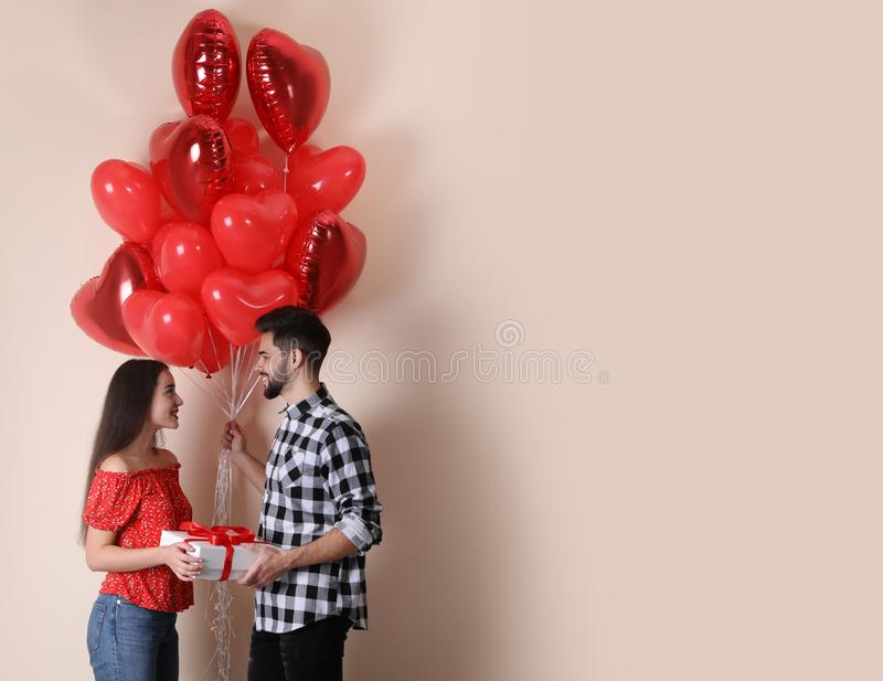 Happy young couple with gift box and heart shaped balloons on background. Valentine`s day celebration royalty free stock photography