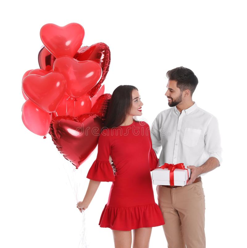 Happy young couple with gift box and heart shaped balloons isolated. Valentine`s day celebration stock photo