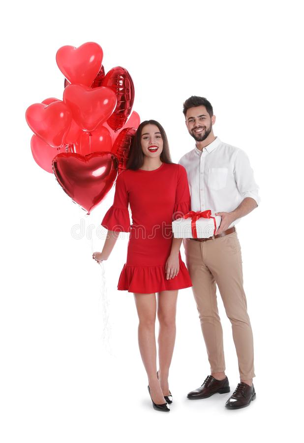 Happy young couple with gift box and heart shaped balloons isolated. Valentine`s day celebration royalty free stock photo