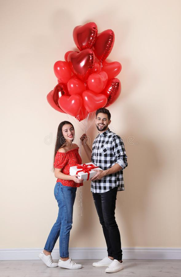 Happy young couple with gift box and heart shaped balloons near wall. Valentine`s day celebration stock image