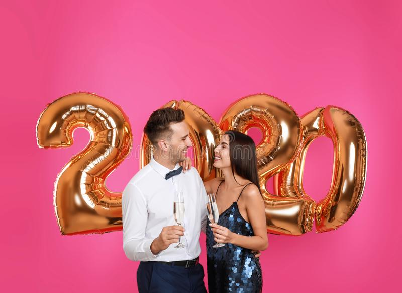 Happy young couple with glasses of champagne near golden 2020 balloons on pink background royalty free stock image