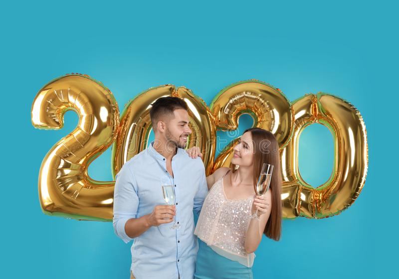 Happy young couple with glasses of champagne near golden 2020 balloons on turquoise background stock photography