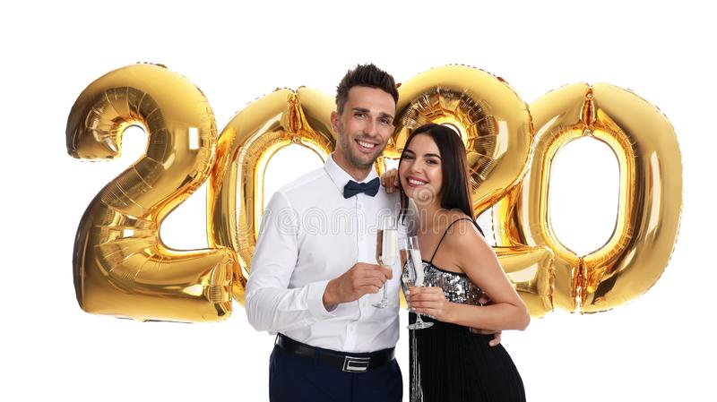 Happy young couple with glasses of champagne near golden 2020 balloons on white background stock images