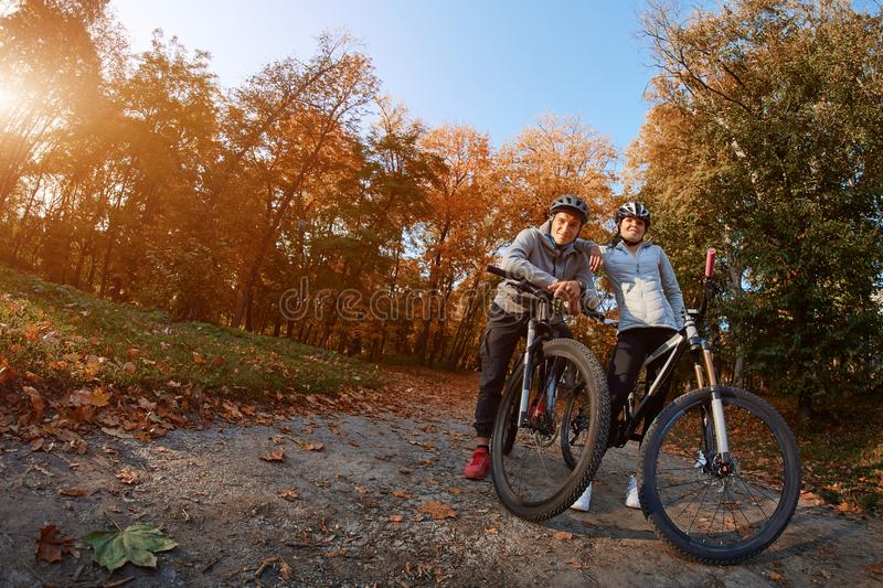 Happy young couple going for a bike ride on an autumn day in the park, backlight. royalty free stock image