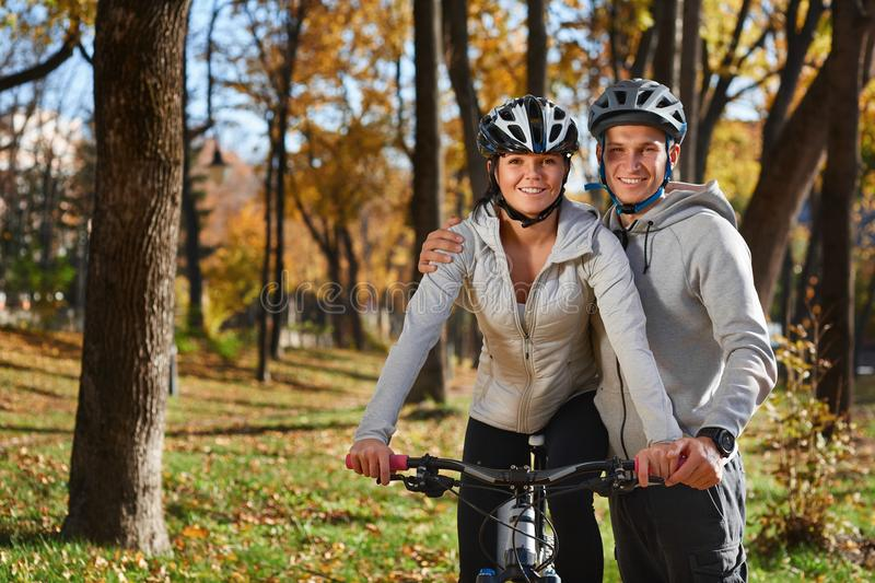 Happy young couple going for a bike ride on an autumn day in the park. stock images