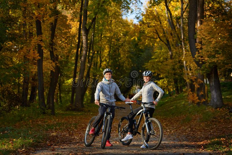 Happy young couple going for a bike ride on an autumn day in the park. royalty free stock photos