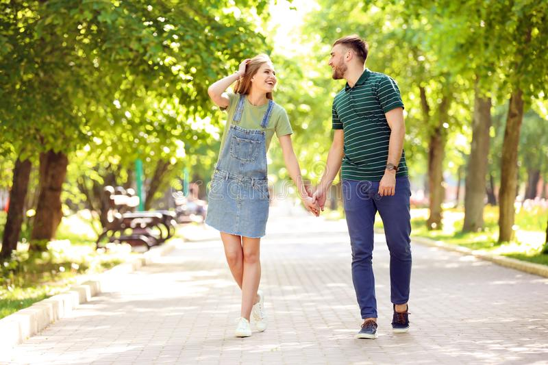 Happy young couple in green park on sunny spring day royalty free stock image
