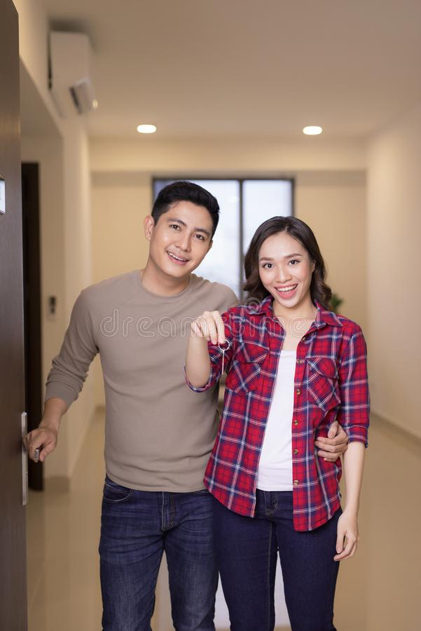 Happy young couple handing their new home keys and open house do. Or royalty free stock image