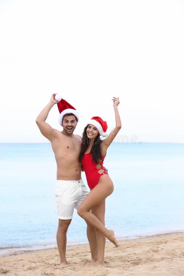 Happy young couple with  hats on beach near sea. Happy young couple with Santa hats on beach near sea royalty free stock photography