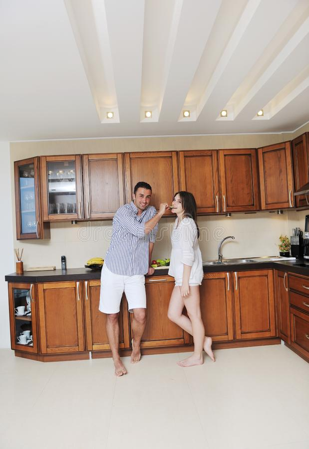 Happy young couple have fun in modern kitchen stock image