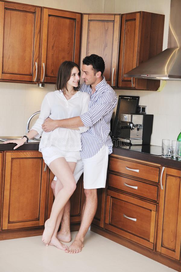 Happy young couple have fun in modern kitchen stock images