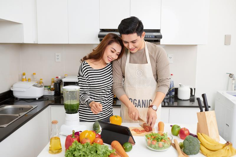 Happy young couple have fun in modern kitchen indoor while preparing vegetables food for lunch royalty free stock photos