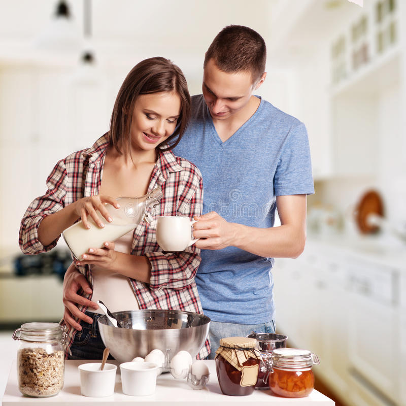 Happy young couple have fun in modern wooden kitchen indoor while preparing fresh food stock images