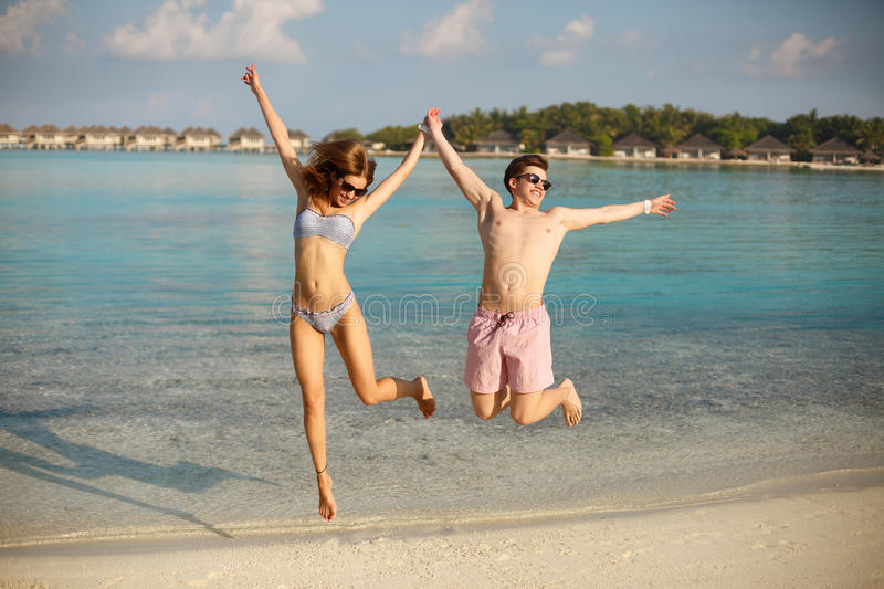 Happy young couple have fun and relax on the beach. Man and woman jump holding hands and smiling. Bungalows of spa royalty free stock photos