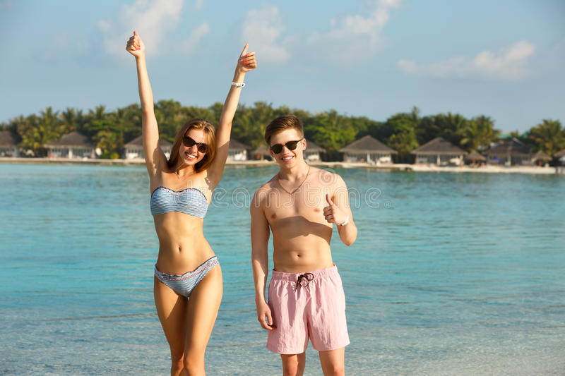 Happy young couple have fun and relax on the beach. Man and woman show thumbs up enjoying vacation near ocean. Bungalows stock image