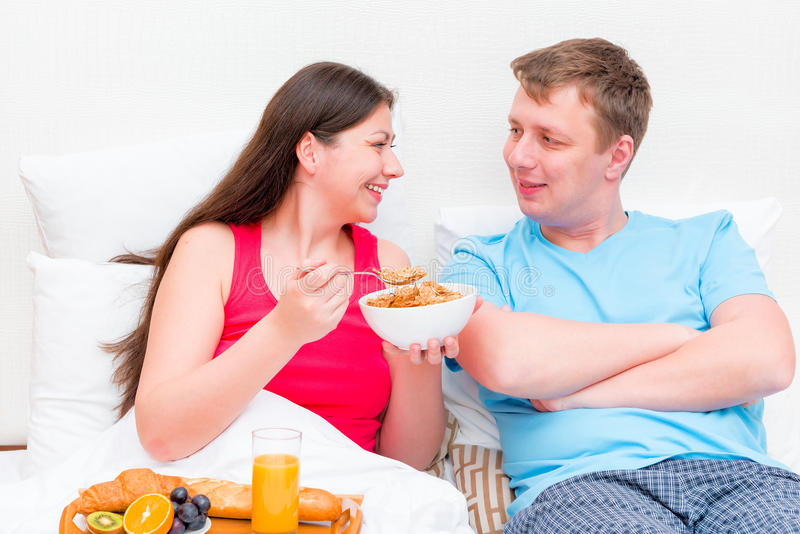 Happy young couple having breakfast stock images