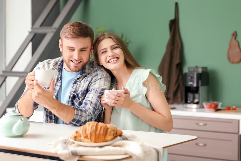 Happy young couple having breakfast in kitchen royalty free stock photography