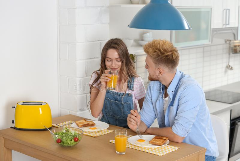 Happy young couple having breakfast at table royalty free stock photo