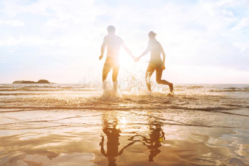 Happy young couple having fun on the beach at sunset, water splash royalty free stock photos