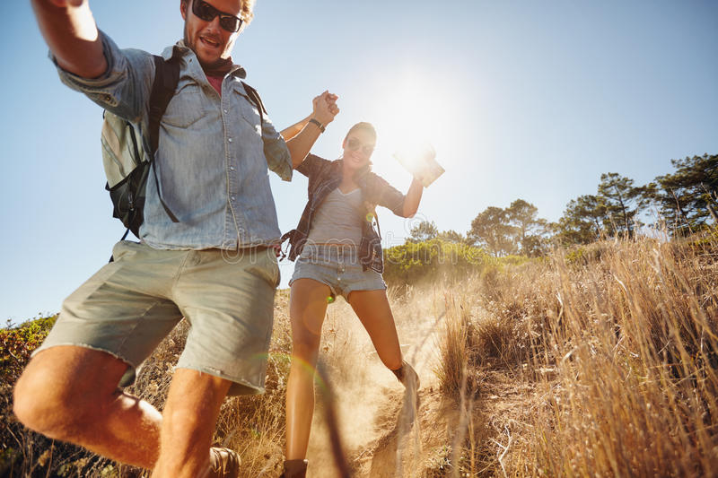Happy young couple having fun on their hiking trip. Portrait of happy young couple having fun on their hiking trip, sliding down the mountain trail. Caucasian