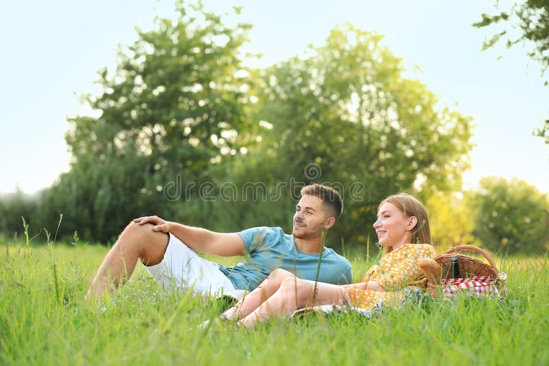 Happy young couple having picnic on green grass royalty free stock images