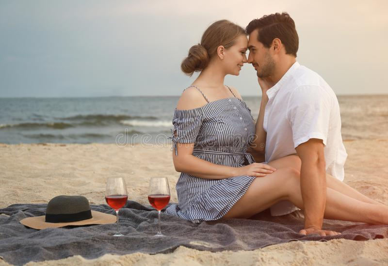 Happy young couple having picnic at sea royalty free stock photo