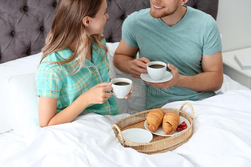 Happy young couple having romantic breakfast in bed royalty free stock photos