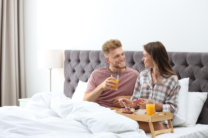 Happy young couple having romantic breakfast in bed stock images