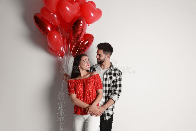 Happy young couple with heart shaped balloons on background. Valentine`s day celebration royalty free stock photos