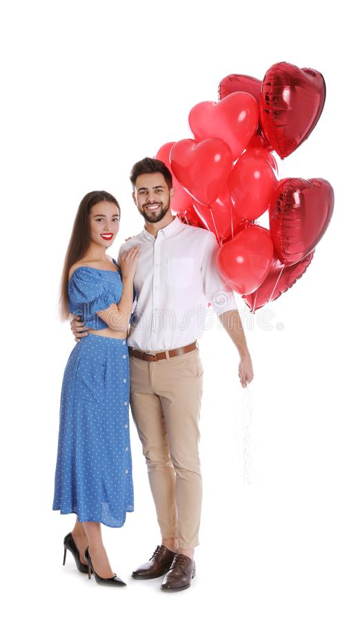 Happy young couple with heart shaped balloons isolated. Valentine`s day celebration royalty free stock image