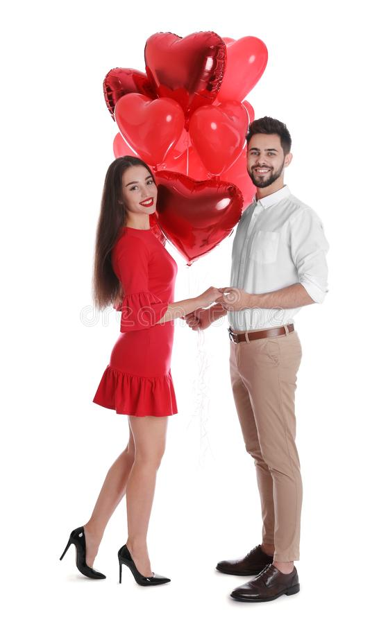 Happy young couple with heart shaped balloons isolated. Valentine`s day celebration royalty free stock photography