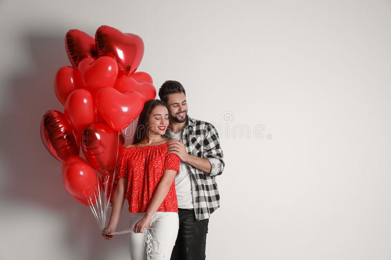 Happy young couple with heart shaped balloons on background, space for text. Valentine`s day celebration royalty free stock photo