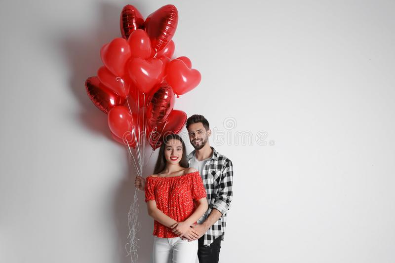 Happy young couple with heart shaped balloons on background. Valentine`s day celebration stock photo