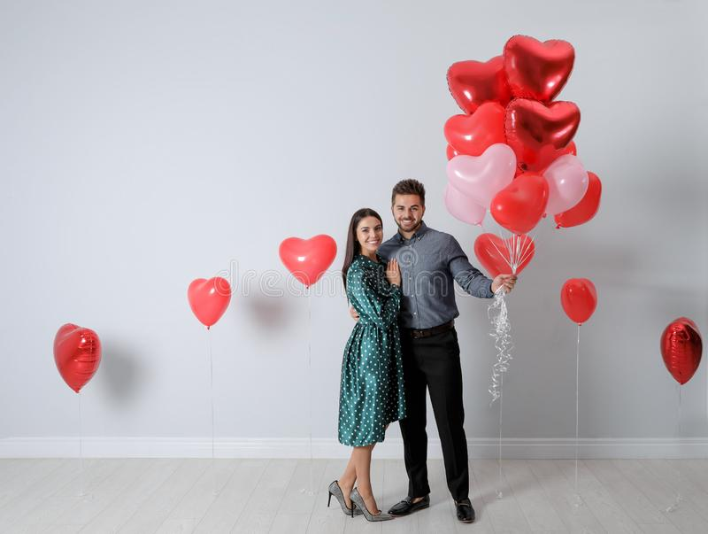 Happy young couple with heart shaped balloons near wall. Valentine`s day celebration. Happy young couple with heart shaped balloons near light wall. Valentine`s stock photography