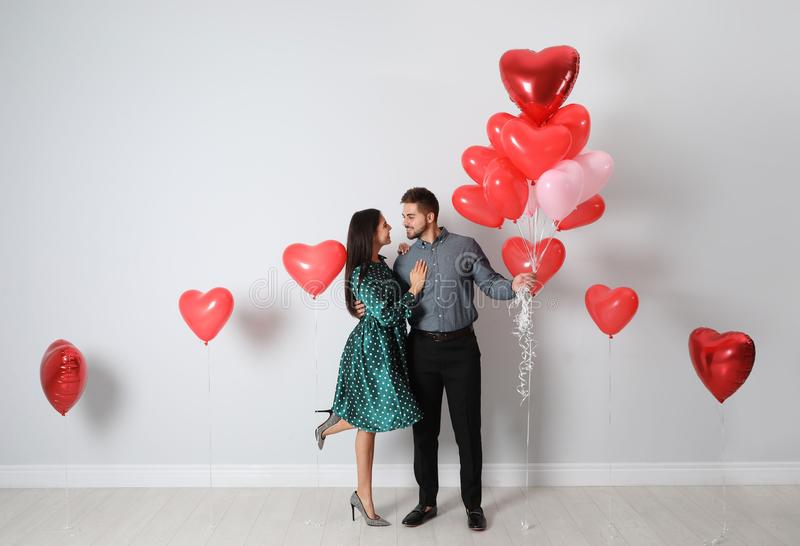 Happy young couple with heart shaped balloons near wall. Valentine`s day celebration royalty free stock photo