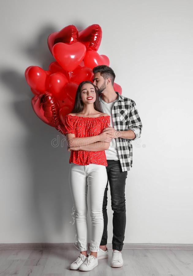 Happy young couple with heart shaped balloons near wall. Valentine`s day celebration stock photos