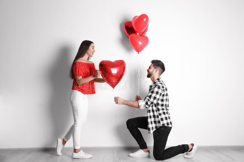 Happy young couple with heart shaped balloons near wall. Valentine`s day celebration royalty free stock image