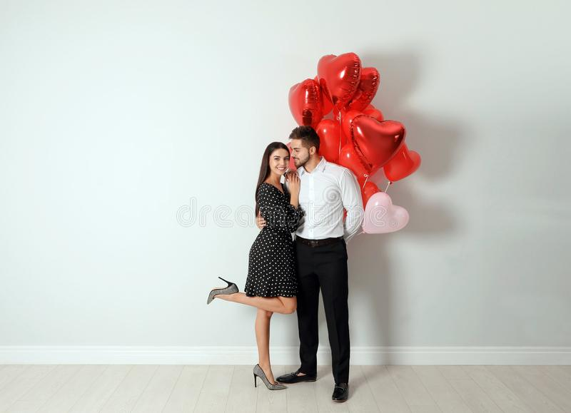 Happy young couple with heart shaped balloons near wall. Valentine`s day celebration. Happy young couple with heart shaped balloons near light wall. Valentine`s stock image