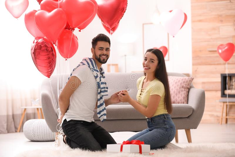 Happy young couple with heart shaped balloons in room. Valentine`s day celebration. Happy young couple with heart shaped balloons in living room. Valentine`s day royalty free stock photos