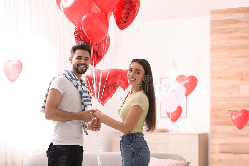 Happy young couple with heart shaped balloons in room. Valentine`s day celebration. Happy young couple with heart shaped balloons in living room. Valentine`s day royalty free stock photography