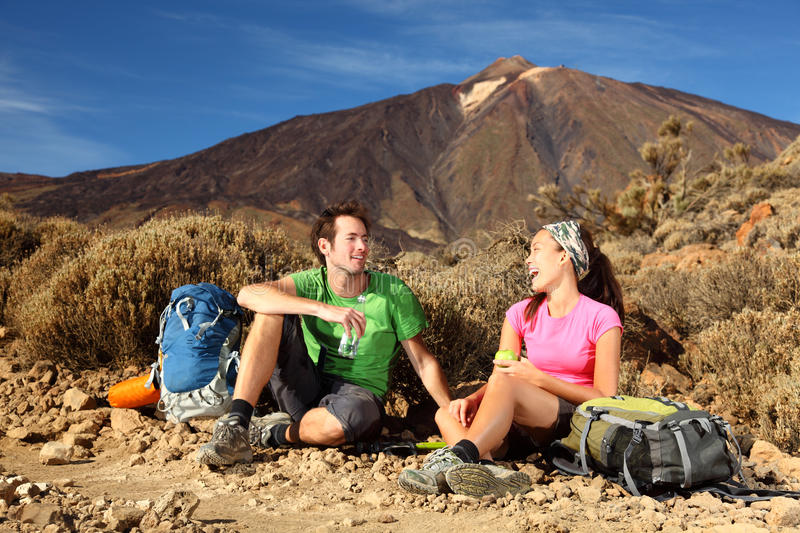Happy Young Couple Hiking. People hiking. Young beautiful couple taking a break, relaxing and eating during a hike / backpacking trip in the beautiful and wild stock photo