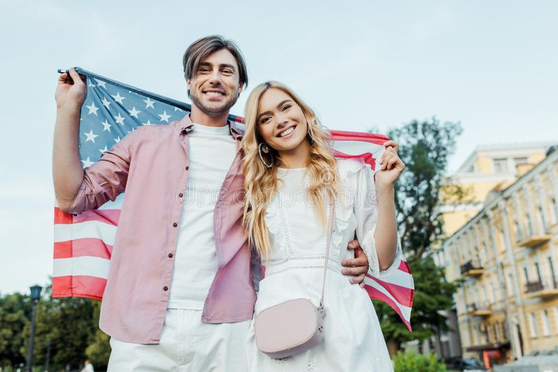 Happy young couple holding american flag in hands Americas Independence. Day concept royalty free stock photo