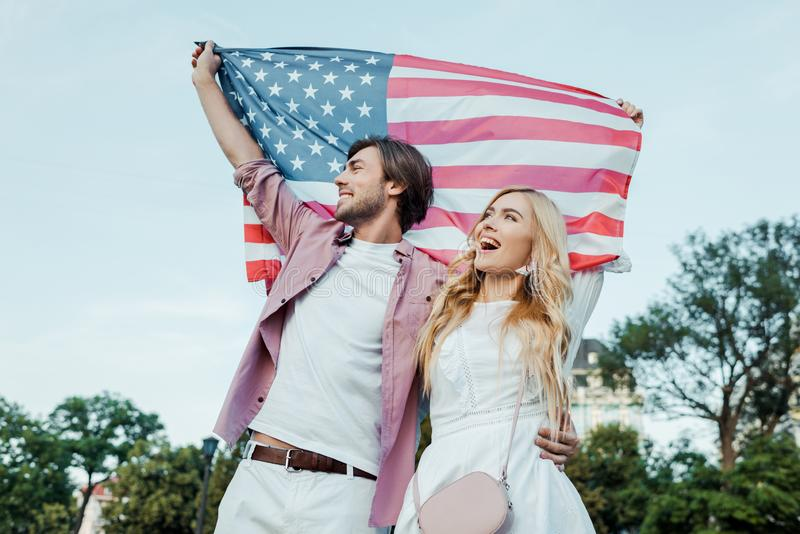 Happy young couple holding american flag in hands Americas Independence. Day concept stock image