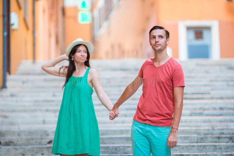 Happy young couple holding hands on Steps in Rome enjoy italian holidays. Happy tourist couple, men and women traveling on holidays in Europe smiling happy stock image