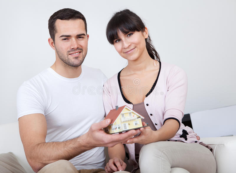 Happy young couple holding a house model stock images